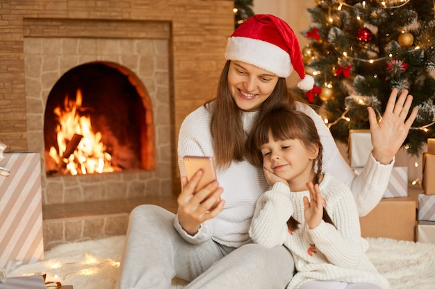 Mom and daughter sitting near christmas tree, hugging, communicating via video call, having fun.