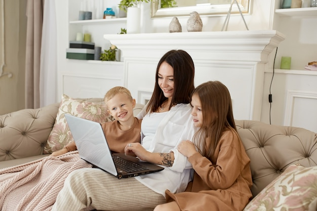 Mom daughter and son play on laptop. family recreation and leisure