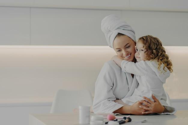 ママ娘のスパ トリートメント。スパでのトリートメントと衛生手順の後、小さな子供のかわいい女の子を抱きしめ、自宅のモダンなキッチンで白いバスローブを着た若い美しい愛情のある母親