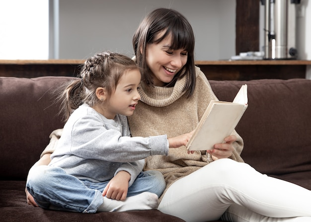 Mom and daughter spend time together reading a book. the concept of children's development and quality time.