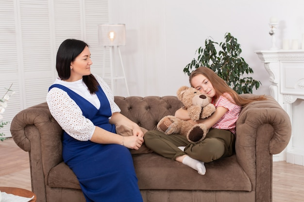 Mom and daughter spend time together, sit on the couch and chat