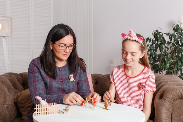 Mom and daughter spend time together, sit on the couch, chatting and playing with toy animals. leisure mothers and daughters