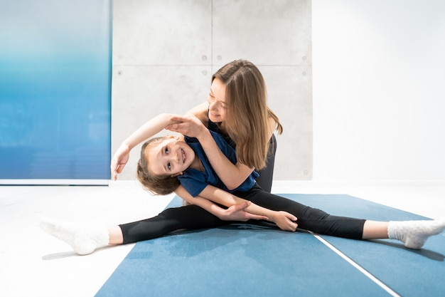 Mom and daughter do stretching before exercise