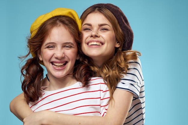 Mom and daughter in the studio posing have fun and smile, happy family, two sisters, the image of france and paris, berets on her head