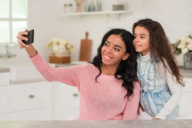 Mom and daughter taking selfies