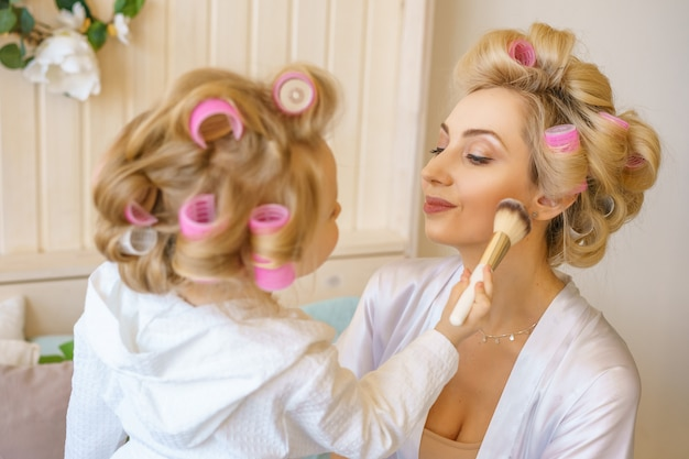 Mom and daughter together happy in curlers
