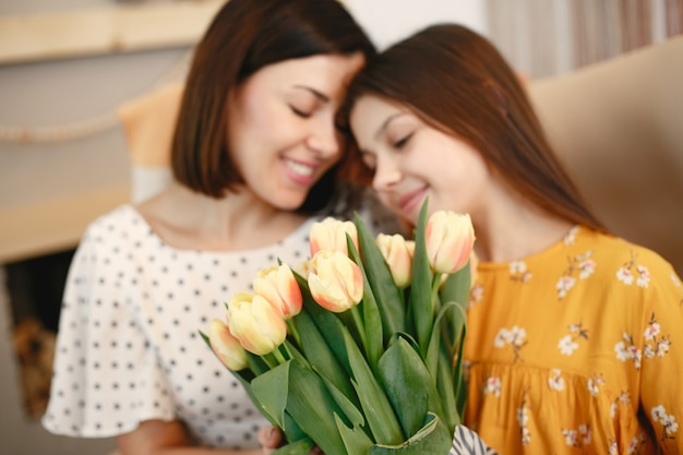 Mom and daughter together holding a tulips bouquet.