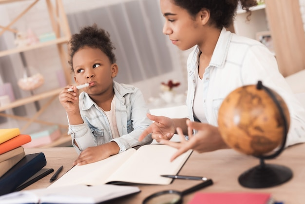 Mom and daughter together do their homework in school.