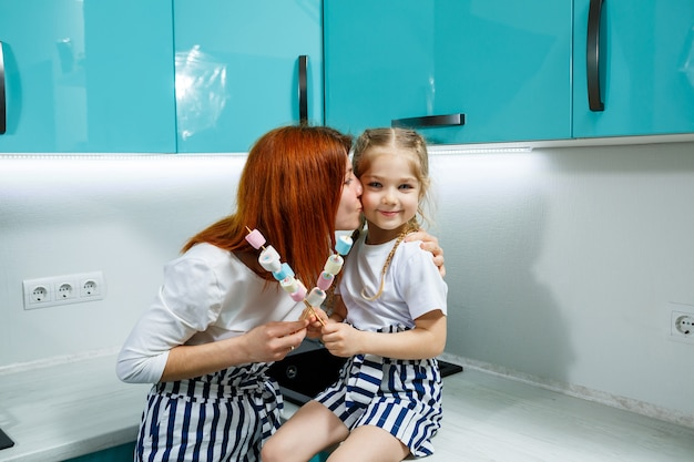 Mom and daughter in the turquoise kitchen are playing with marshmallows. lovely family relationships. happy family concept