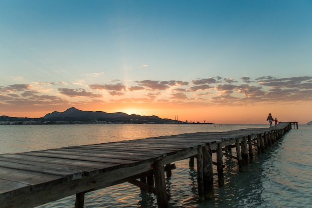 Mom and daughter walk along the pier towards the amazing and beautiful sunrise on the island of mallorca