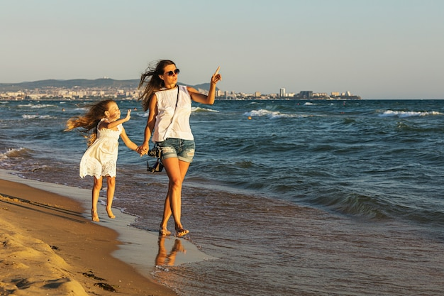 Mom and daughter walk on the beach on a sunny summer evening