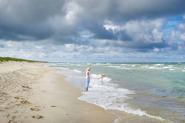 Mom and daughter walk together along the shores of the baltic sea in lithuania.