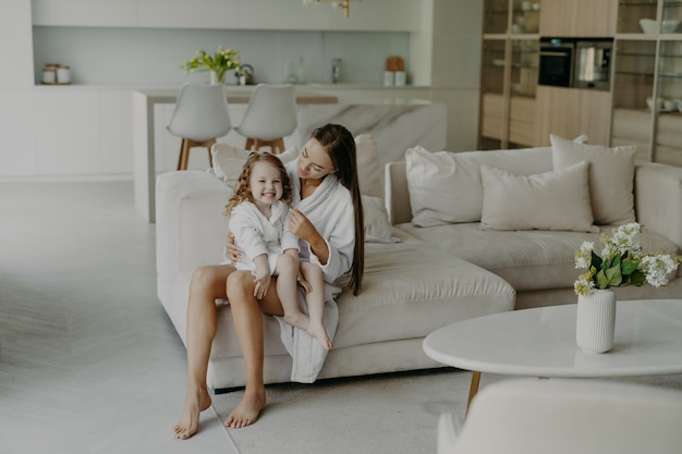 Mom and daughter wear domestic clothes sit on comfortable sofa in living room.