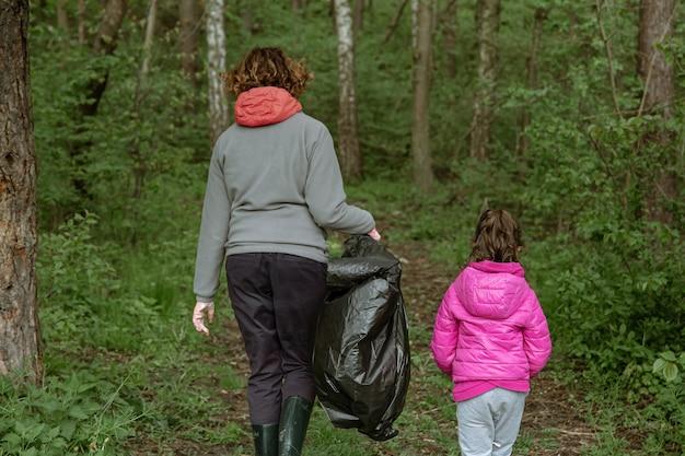 Mamma e figlia con i sacchetti della spazzatura puliscono l'ambiente dalla spazzatura.