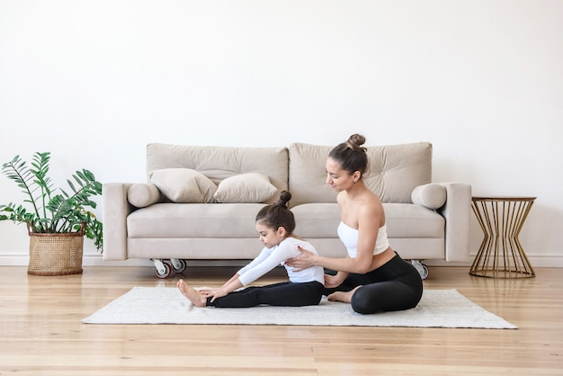 Mom and daughter do yoga stretching gymnastics together at home