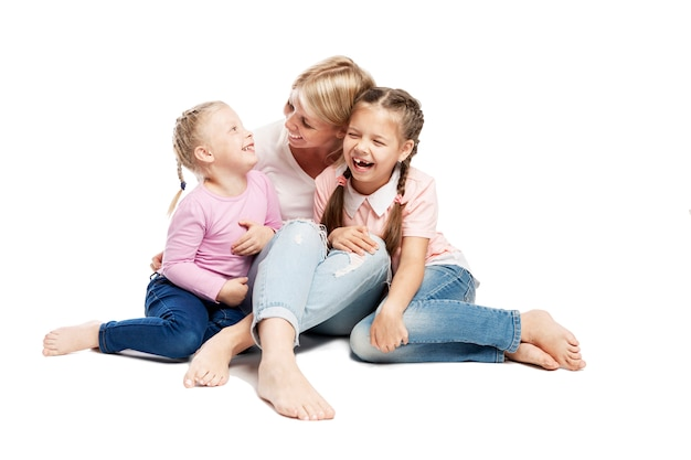 Mom and daughters are sitting and laughing. love and tenderness. isolated over white background.