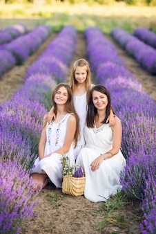 Mom and daughters in a lavender field. summer photo in purple colors.