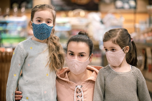 Mom and daughters shop in masks at the store during quarantine due to the coronavirus pandemic close up.