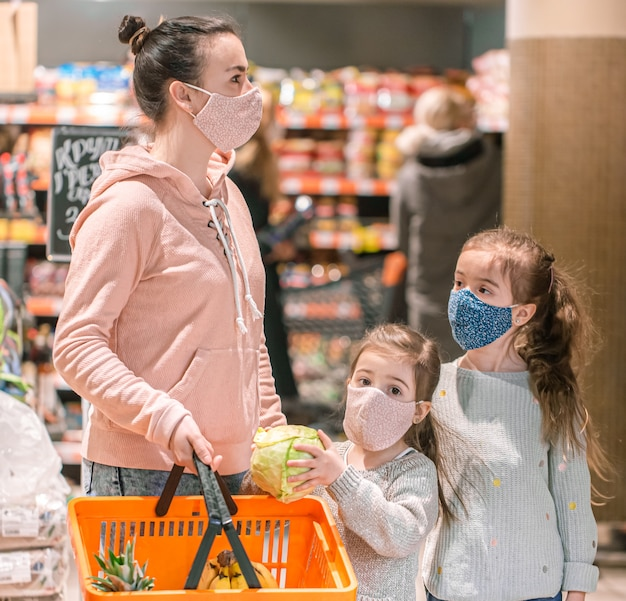 Mom and daughters shop in masks at the store during quarantine due to the coronavirus pandemic.