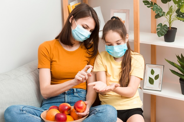 Mom desinfecting fruits for girl before eating