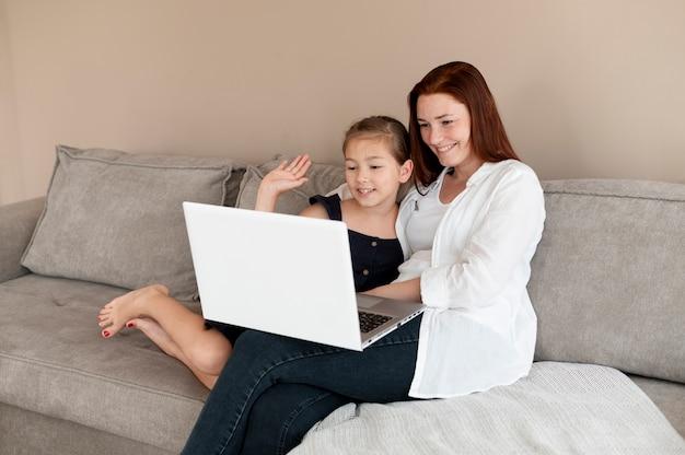 娘と家族のビデオ通話をしているお母さん