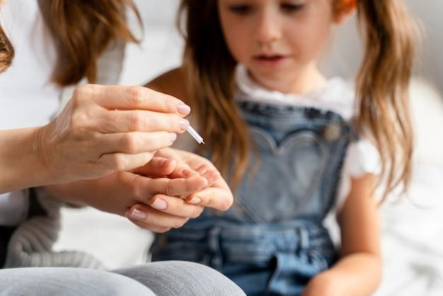 그녀의 딸에게 가정 covid 테스트를하는 엄마