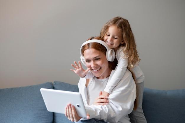 Mamma fa una videochiamata di famiglia con sua figlia