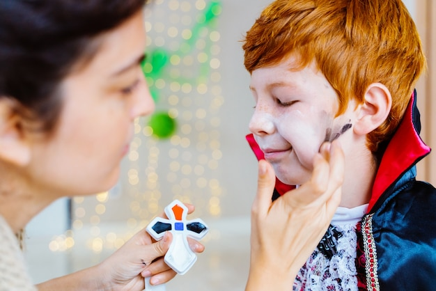 Mom doing vampire makeup to little kid at home for halloween spooky costume party
