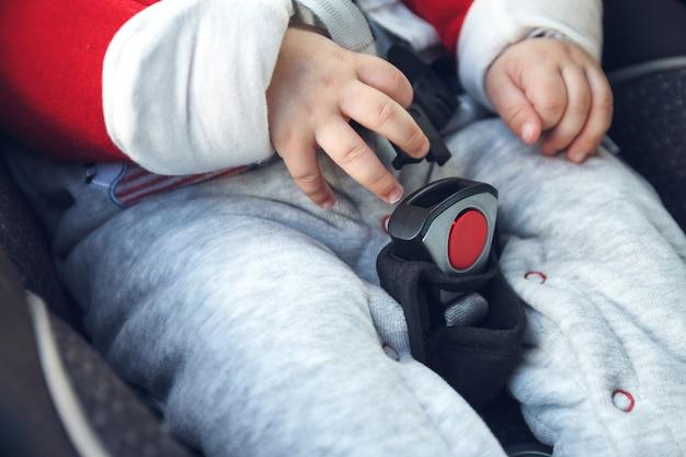 ママは小さな子供が座っているチャイルドシートに安全ベルトを締めます