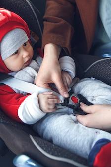 엄마는 어린 아이가 앉은 카시트에 안전 벨트를 매다