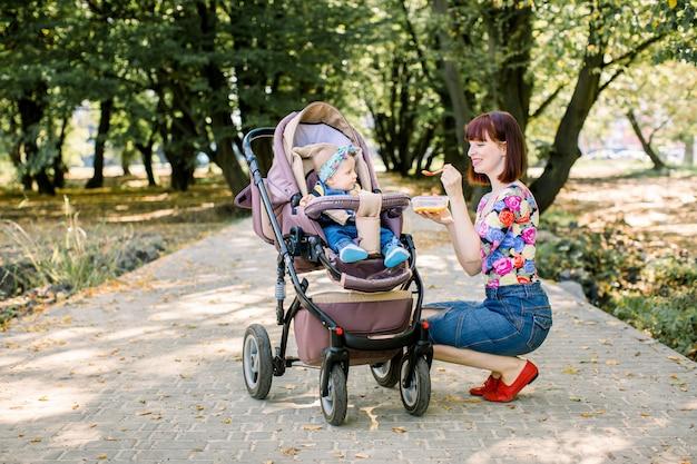 スプーンで彼女の女の赤ちゃんを授乳するママ。母親が公園でベビーカーで歩く10か月の子供に食べ物を与えます。ベビーフード。