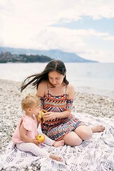 ママはビーチに座っている間、小さな女の子にバナナを与えます