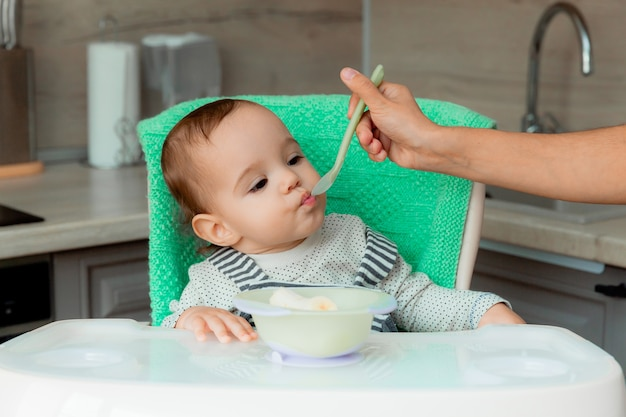 ママはスプーンで赤ちゃんを養います。生後12ヶ月のかわいい赤ちゃんがハイチェアに座ってバナナを食べます。