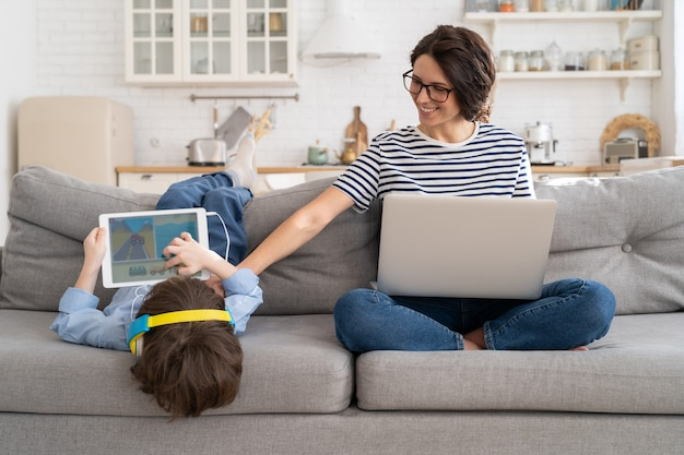 Mom freelancer remote work from home office on laptop sit on couch child playing on tablet lockdown