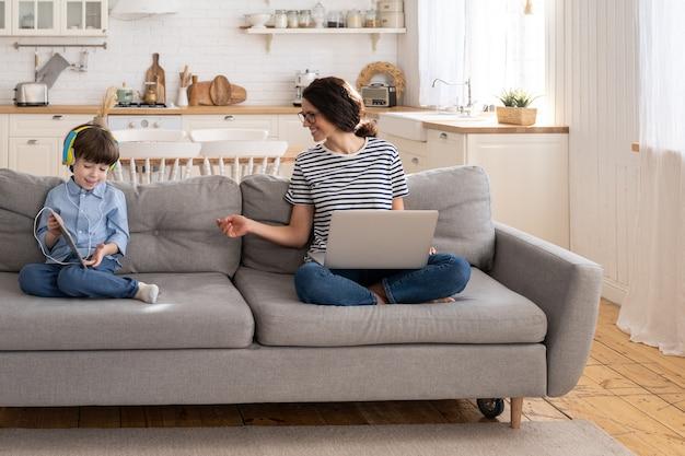 ラップトップ上のホームオフィスからのママフリーランサーリモートワークは、タブレットで遊んでいるソファの子供に座っています。封鎖