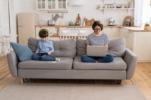 ノートパソコンのホームオフィスからリモートで作業しているママのフリーランサーは、タブレットのロックダウンで遊んでいるソファの子供に座っています