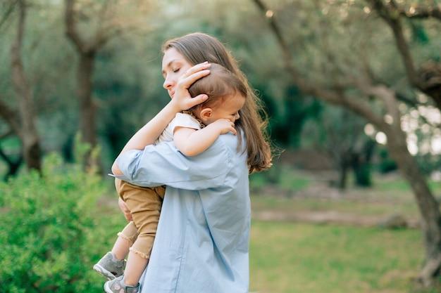 엄마는 올리브 과수원에있는 나무를 마주보고 그녀의 작은 아들을 팔에 부드럽게 안고 있습니다.
