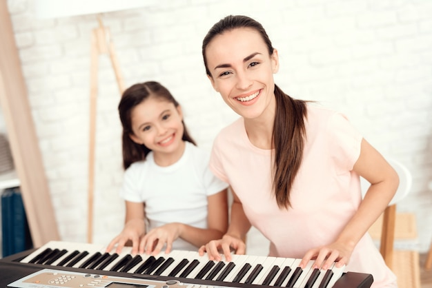 Mom and girl are playing on piano and rest and have fun.