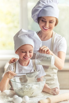 Mom and girl are smiling while preparing the dough