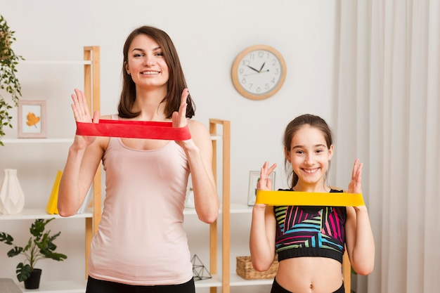Mom and girl exercising with elastic band