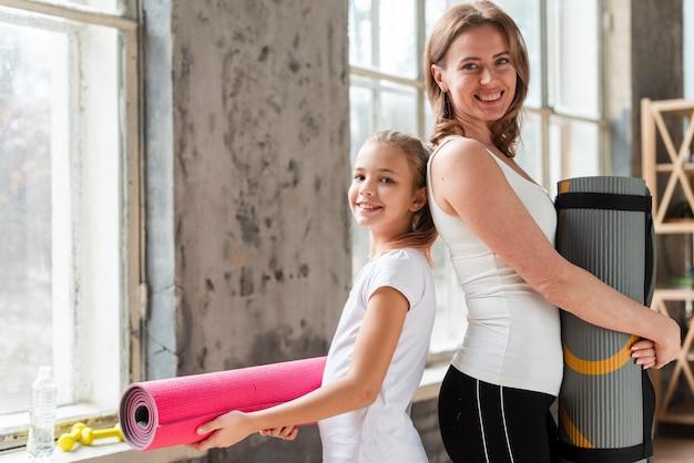 Mom and girl holding yoga mats