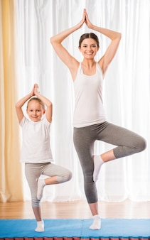 Mom and girl stand on one leg and raised their hands up.