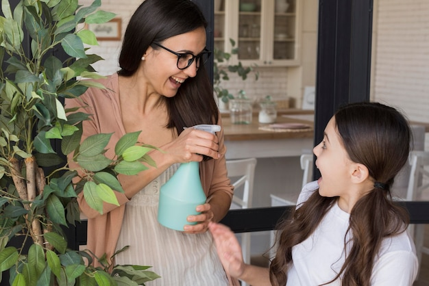 Mom and girl watering plant