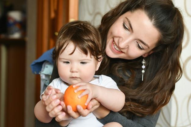 Мама дает ребенку апельсин. витамины для ребенка. фрукты для детей. здоровое питание