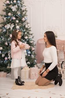 Мама дарит любимой дочери коробку с рождественским подарком.