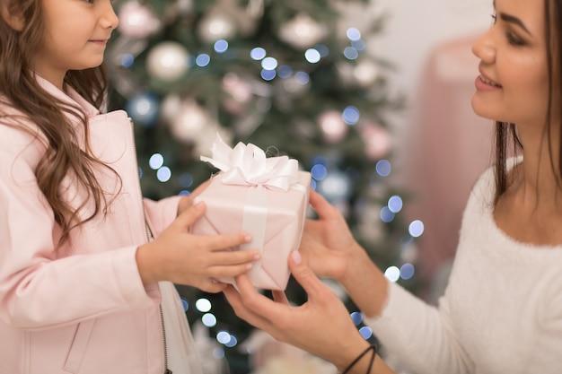 Мама дарит любимой дочке коробку с рождественским подарком.