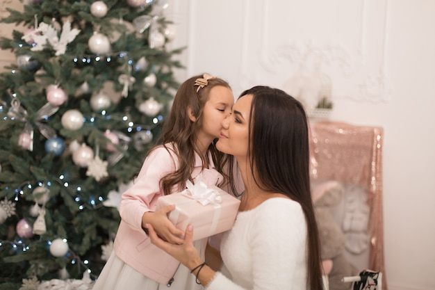 Mom gives her beloved daughter a box with a christmas present