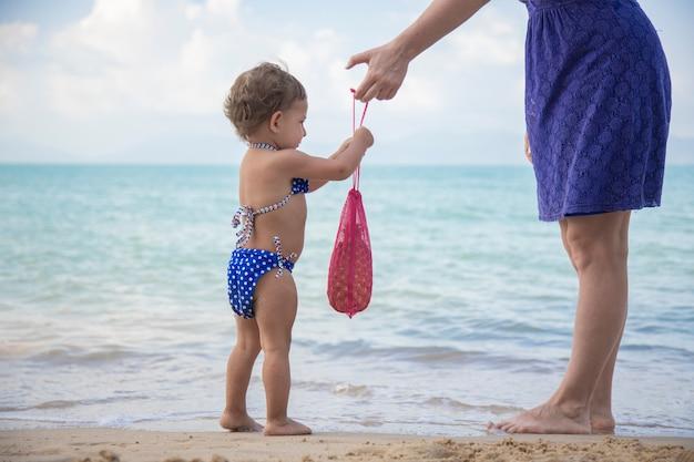 Мама дарит своему ребенку сетчатую сумку на морском пляже. экология культура с малых лет