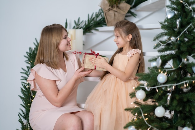 Mom gives her daughter a christmas present from santa christmas magic