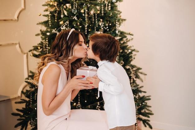 ママは息子にクリスマスツリーの近くでクリスマスプレゼントを贈ります。幸せな家族。